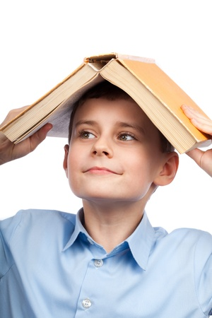 Schoolboy holding a big book on his head photo