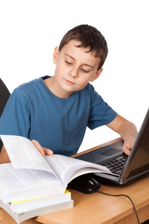 education technology: Portrait of a boy doing his homework at the laptop, isolated on white background