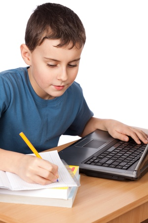 Portrait of a boy doing his homework at the laptop, isolated on white background photo