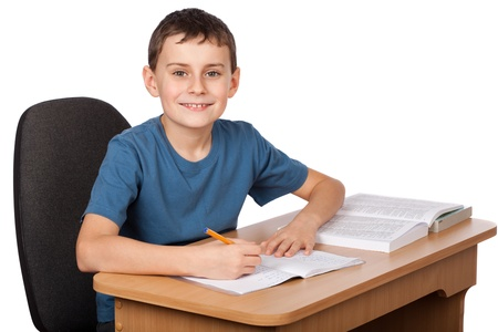 sitting at desk: Schoolboy doing his homework at his desk Stock Photo