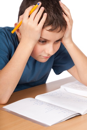 Schoolboy being stressed by his homework, isolated on white background photo