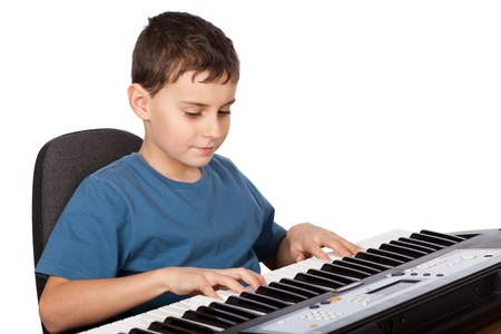 Cute kid playing piano, isolated on white background photo