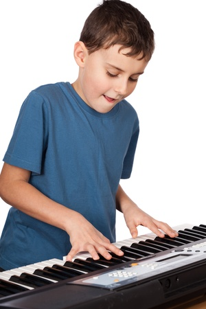 piano lesson: Cute kid playing piano, isolated on white background