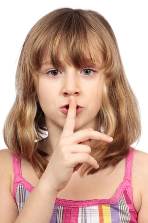 Closeup portrait of a little girl making silence sign with finger on her lips photo