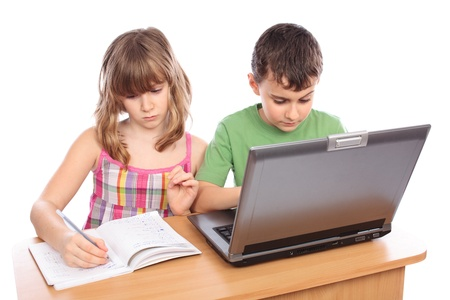 Two school children doing homework together with computer, isolated on white background Stock Photo