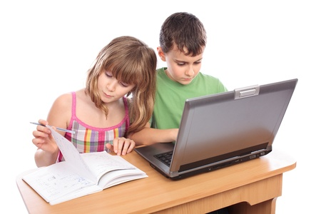 elementary students: Two school children doing homework together with computer, isolated on white background Stock Photo