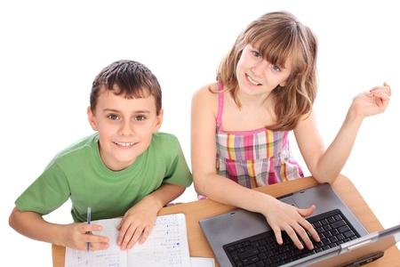 ni�os rubios: Dos ni�os de escuela haciendo tareas junto con el equipo, aislado en fondo blanco Foto de archivo