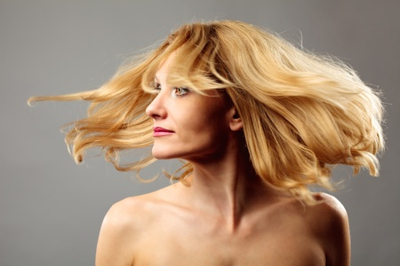 Studio closeup portrait of a blond woman flipping her hair photo