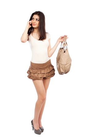 Full length portrait of a beautiful hispanic woman with a purse speaking on cellphone photo