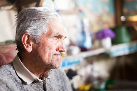 Indoor closeup portrait of an expressive senior farmer with selective focus photo
