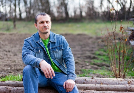Portrait of a handsome young farmer sitting on a pile of logs, with ploughed land in background photo