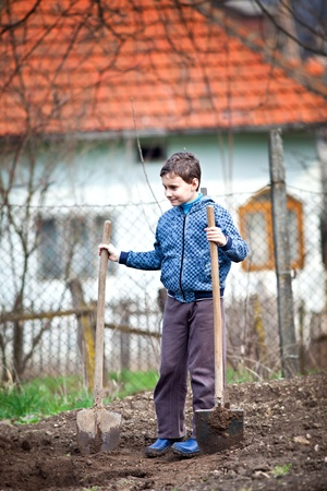 boy with a shovel digging in the garden photo