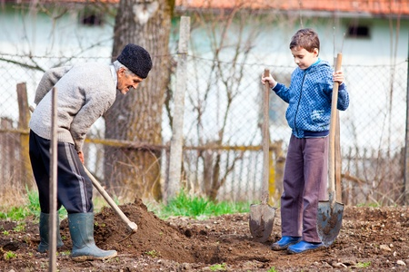 agricultural tools: Senior farmer teaching his grandson how to plant trees in the garden