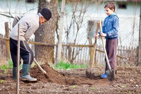 Senior agricultor enseña a su nieto a plantar árboles en el jardín Foto de archivo