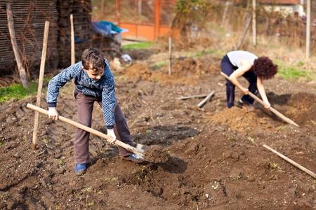Madre e hijo de excavación para plantar árboles en el jardín Foto de archivo