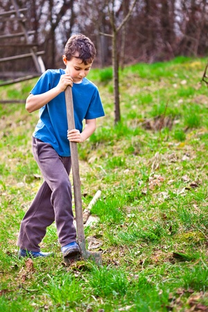 boy with a shovel digging in the garden Stock Photo - 9412655