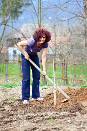 Young redhead woman digging into her garden for planting trees photo
