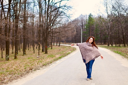 Young redhead lady standing in the middle of the road in a forest Stock Photo - 9412304