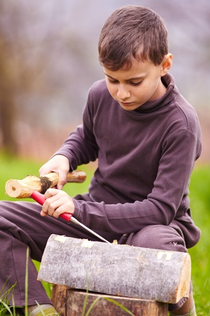 bark carving: Boy sculpting with a chisel into the bark of a beech log outdoor Stock Photo