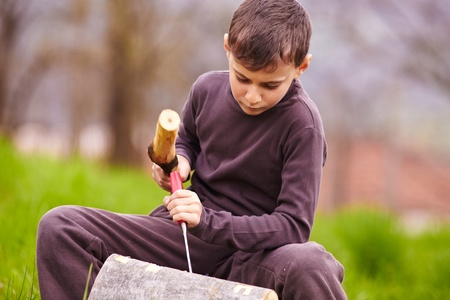 Boy sculpting with a chisel into the bark of a beech log outdoor photo