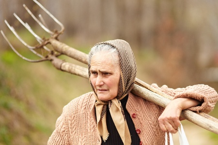 Old farmer woman carrying a fork, outdoor