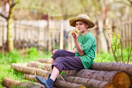 candid: Portrait of a happy boy with a straw hat sitting on a pile of pine logs