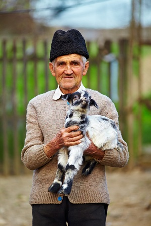 candid: Senior farmer holding a baby goat outdoor
