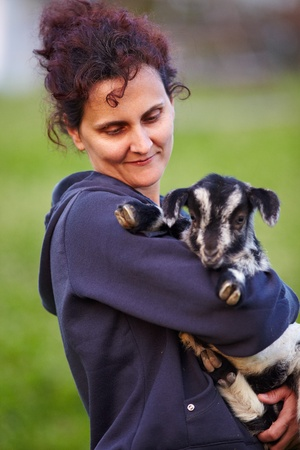 Portrait of a young woman holding a baby goat outdoor photo