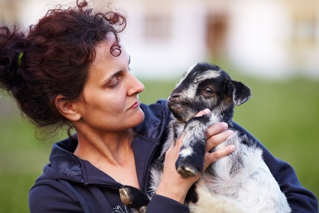 Portrait of a young woman holding a baby goat outdoor Stock Photo - 9502183
