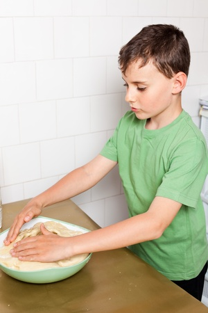 Little boy kneading pizza or bread dough photo