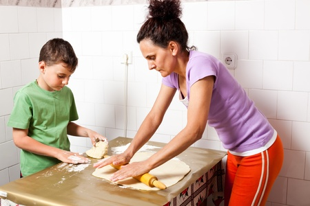 Mother and son cooking pizza or cookies together photo