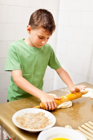 Portrait of a little boy in the kitchen using rolling pin to prepare the dough for cookies photo