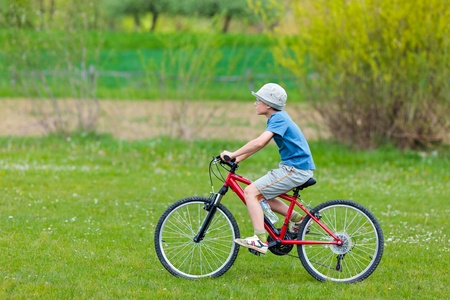 bicycling: Boy with hat riding a bicycle on a grass field Stock Photo