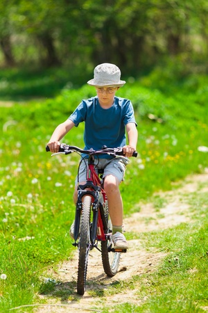Boy with hat riding a bicycle on a grass field Stock Photo - 9538848