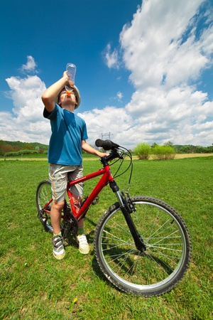 Boy on a bicycle stopped to have a break and drink water photo