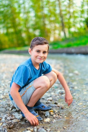 river banks: Boy in shorts, t-shirt and slippers playing with pebbles on a river bank