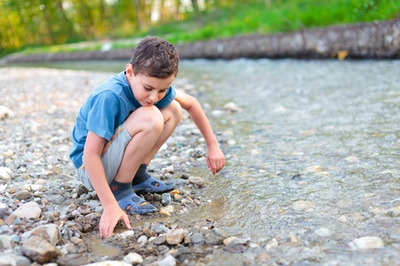 river bank: Boy in shorts, t-shirt and slippers playing with pebbles on a river bank