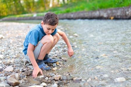 shorts: Chico en shorts, camiseta y zapatillas jugando con guijarros en una ribera del r�o