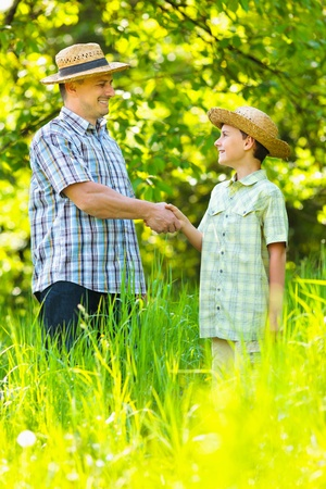 sone: Father and sone outdoor in an orchard, shaking hands