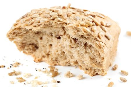 miettes: Vue rapproch�e de grains entiers pain avec des graines de tournesol isol� sur fond blanc Banque d'images