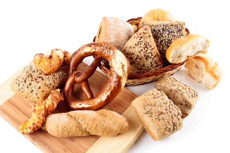 Various assortment of whole grain bread on a wooden board and basket