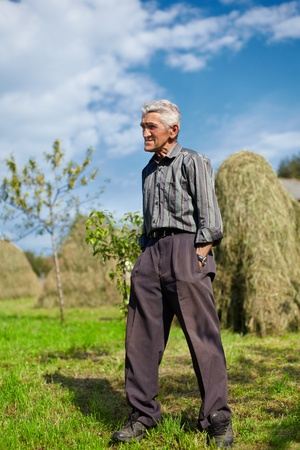 thin man: Full length portrait of a senior farmer on a meadow with hay stacks in background Stock Photo