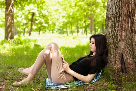person outside: Attractive young woman reading a book outdoor in the forest