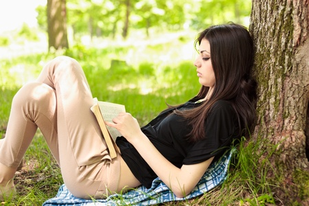 Attractive young woman reading a book outdoor in the forest
