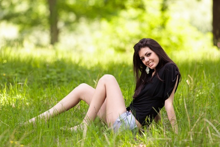 Portrait of a beautiful young latin woman sitting in grass in a forest