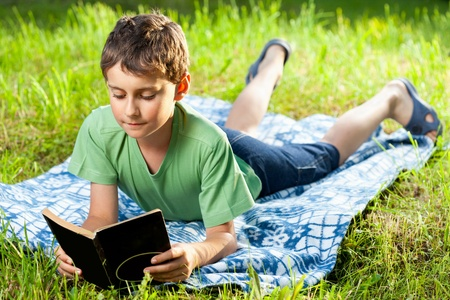 Portrait of a boy reading a book outdoor on the grass Stock Photo
