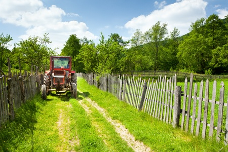 Old red tractor in the countryside on a rural road Stock Photo - 9849889