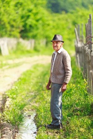 Old farmer outdoor, full length portrait photo
