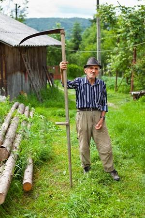 guada�a: Farmer senior con guada�a para cortar el c�sped tradicionalmente Foto de archivo