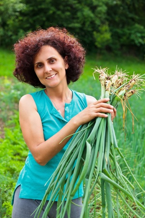 Young farmer woman with a sheaf of young onions in her garden photo